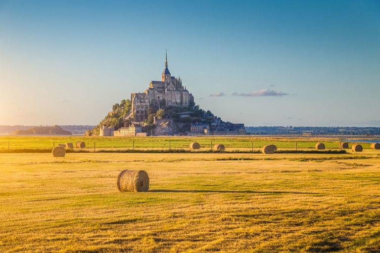 Un champ avec des rouleaux de foin et derrière le majestueux Mont Saint Michel lors d'une escapade en Normandie, des offres sur-mesure pour les familles, groupes d'amis, scolaires, entreprises et associations
