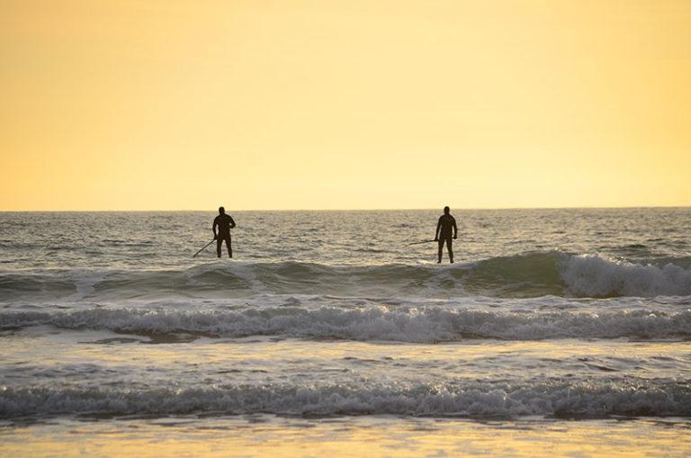 Deux hommes en paddle sur la mer de la Manche lors d'une balade eco-responsable avec On se met au vert